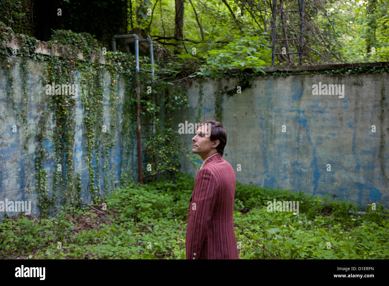 Man in Overgrown Abandoned Place - Stock Image