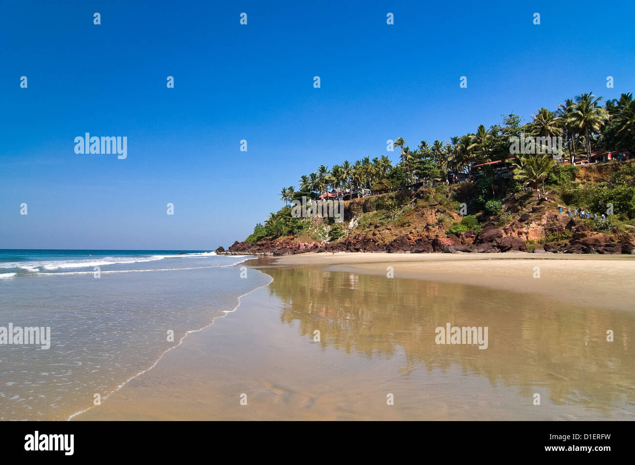 Horizontal view of the unique cliffs on Papanasam beach reflected in the wet sand at Varkala, Kerala. - Stock Image