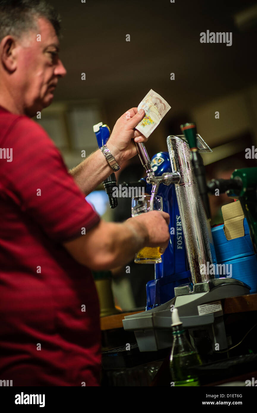 A barman pulling a pint of cold lager and holding a £10 note on a Saturday night, in a working mens club, UK - Stock Image