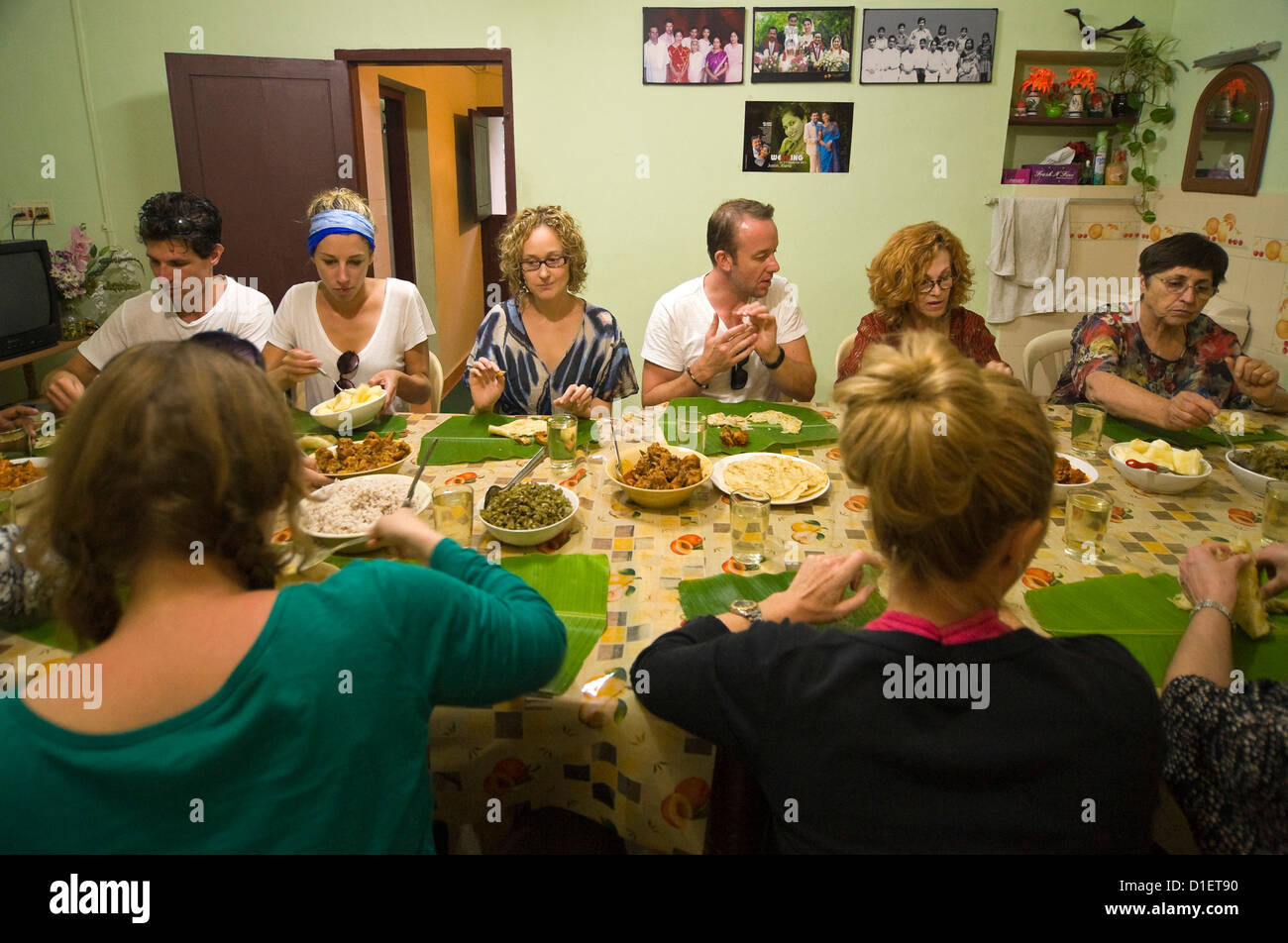 Horizontal portrait of Western tourists eating Indian meal using fingers instead of cutlery and banana leaves instead - Stock Image