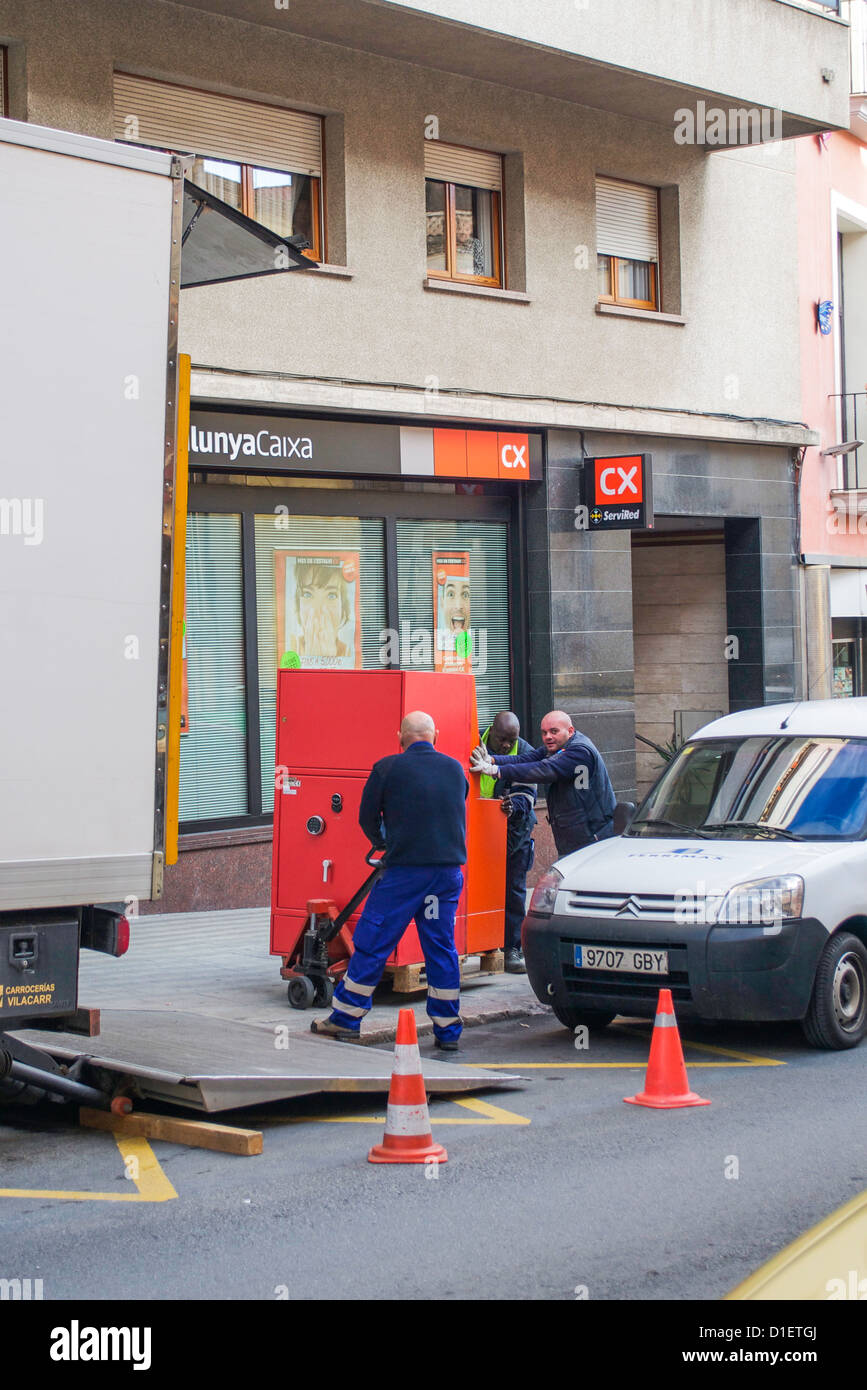 Three men struggle to move a heavy safe, just taken out of the bank in back of them, up a ramp and into a truck - Stock Image
