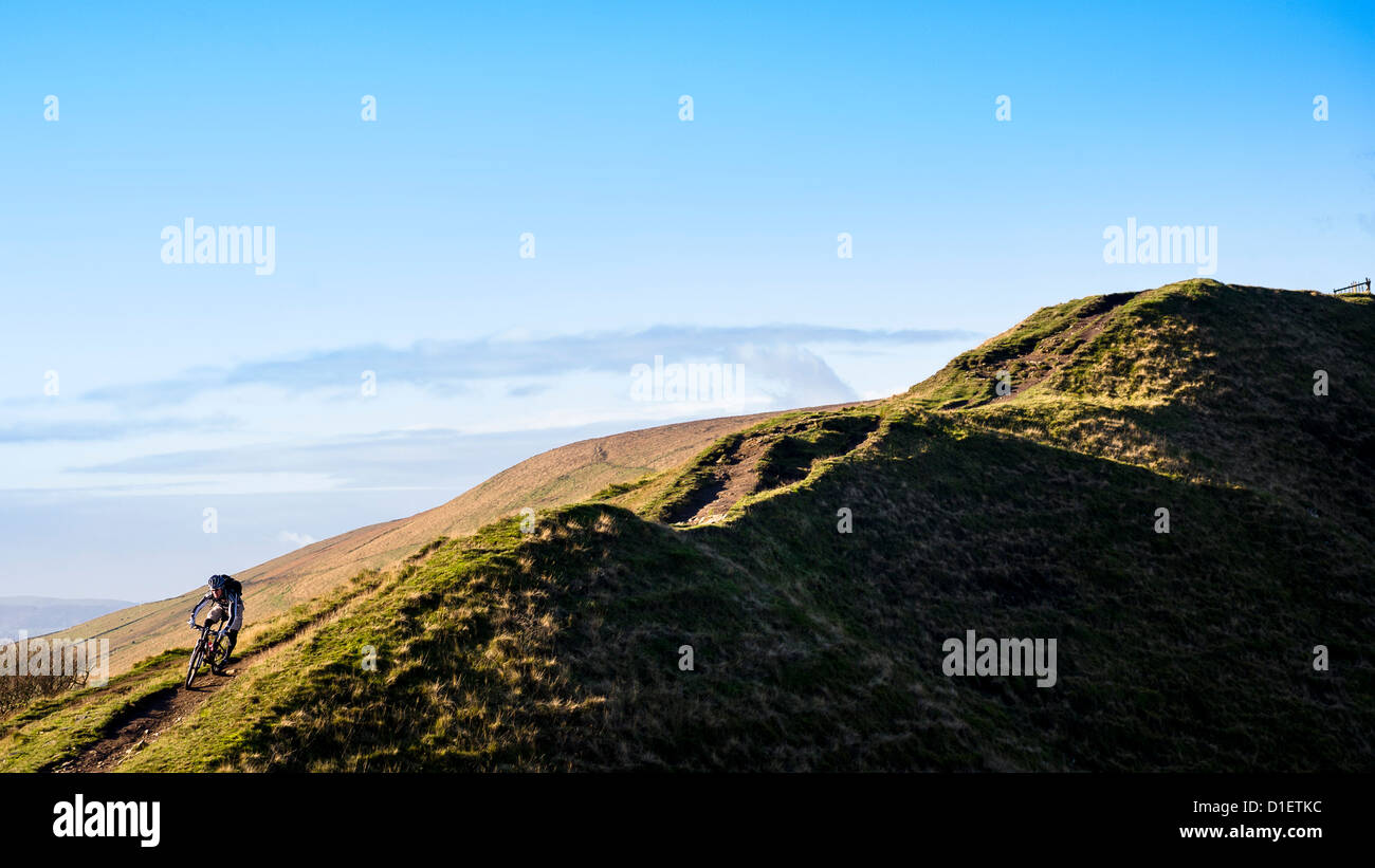 Mountain biker rides down a hilly trail in the Peak District, England, United Kingdom Stock Photo