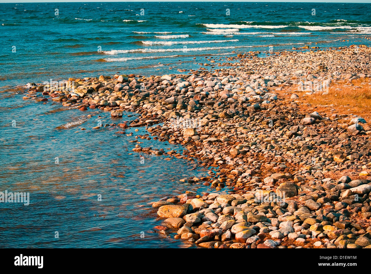 Coastline with waves lapping up against stony beach - Stock Image