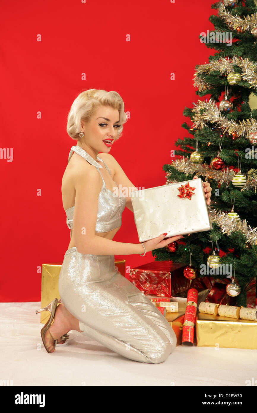 Woman in retro silver outfit holding a present by the Christmas tree - Stock Image