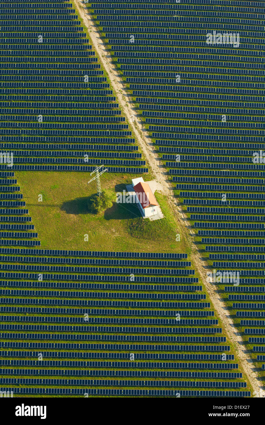 Solar panels, house and electricity pylon on a field, aerial photo - Stock Image