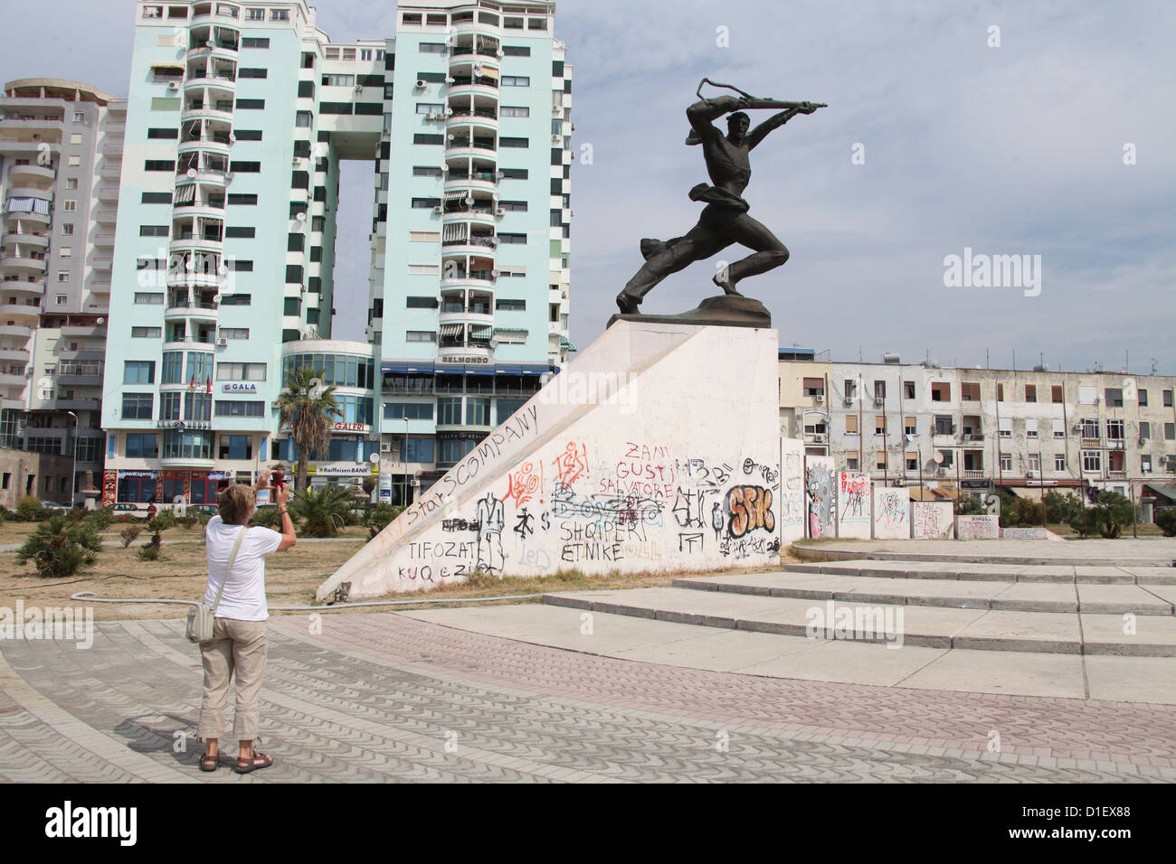 Tourist Photographing the Socialist Realism Statue of a Soldier at Durres in Albania - Stock Image