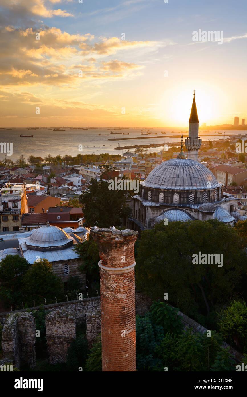 Setting sun behind the Sokollu Mehmet Pasha mosque minaret and historic Dervish ruins on the Marmara Sea Istanbul - Stock Image
