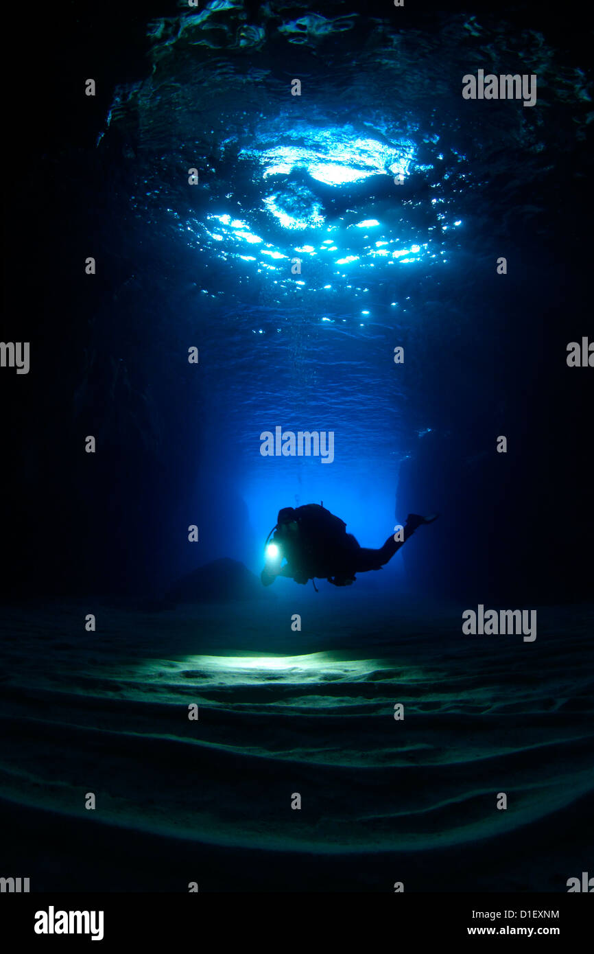 Diver in the entry of a cave, Mediterranean Sea near Gozo, Malta, underwater shot - Stock Image