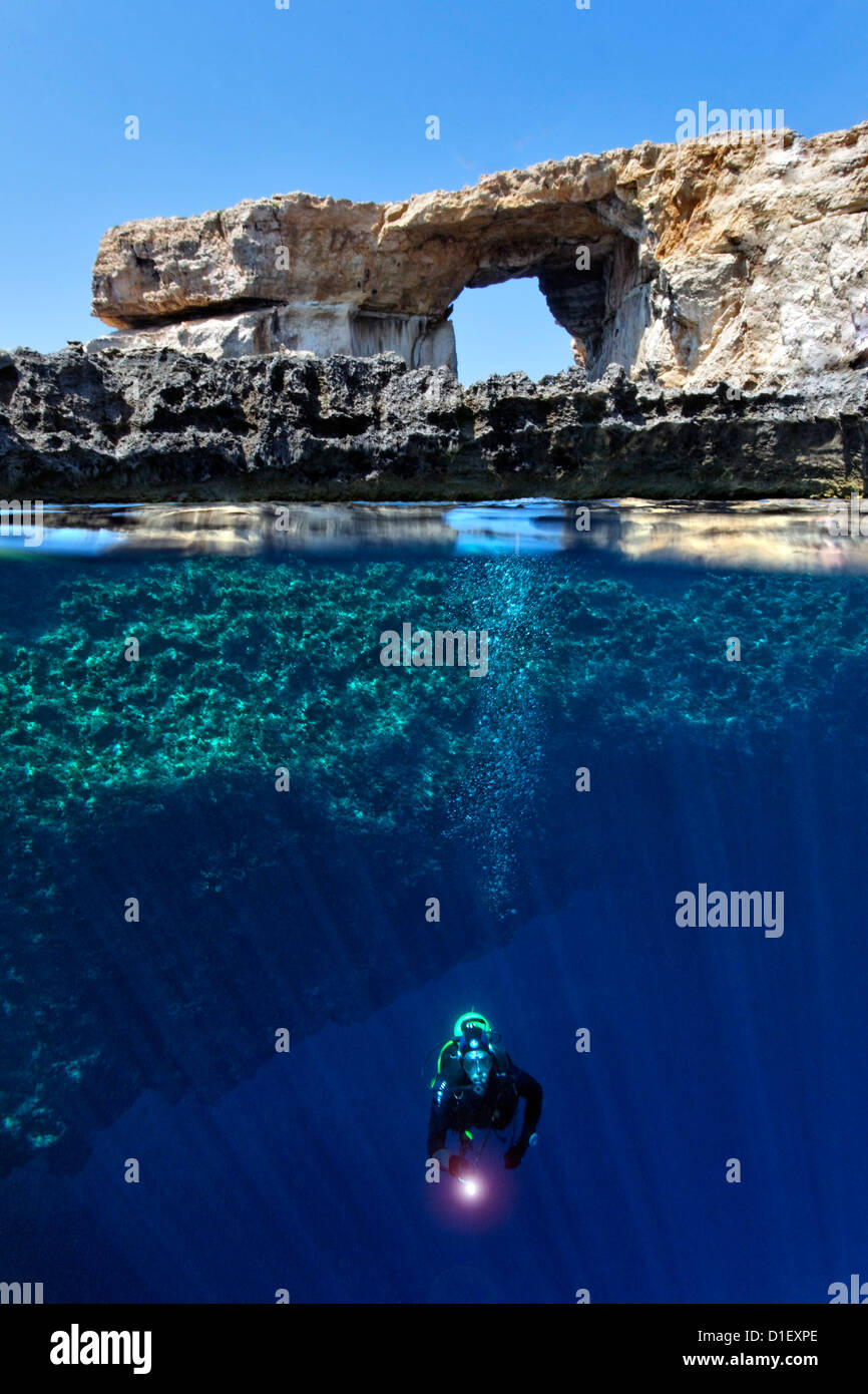 Split shot half and half with diver and rock arch Azure window in the Mediterranean Sea near Gozo, Malta - Stock Image
