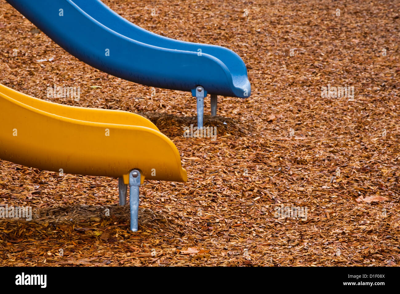 Abstract image of two childrens slides at a vacant playground - Stock Image