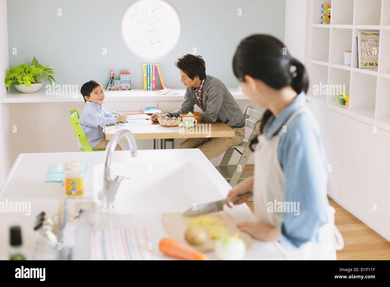Mother cooking in an open kitchen watching father and son doing ...