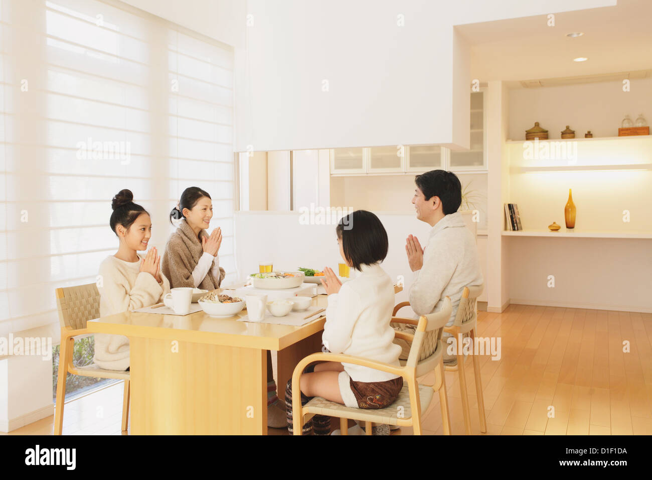 Family Of Four People Eating At The Dining Table In The Living Room