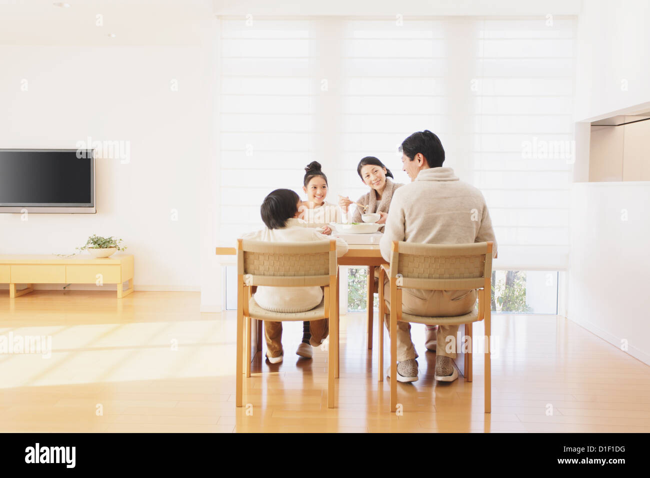 Family of four people eating at the dining table in the living room ...