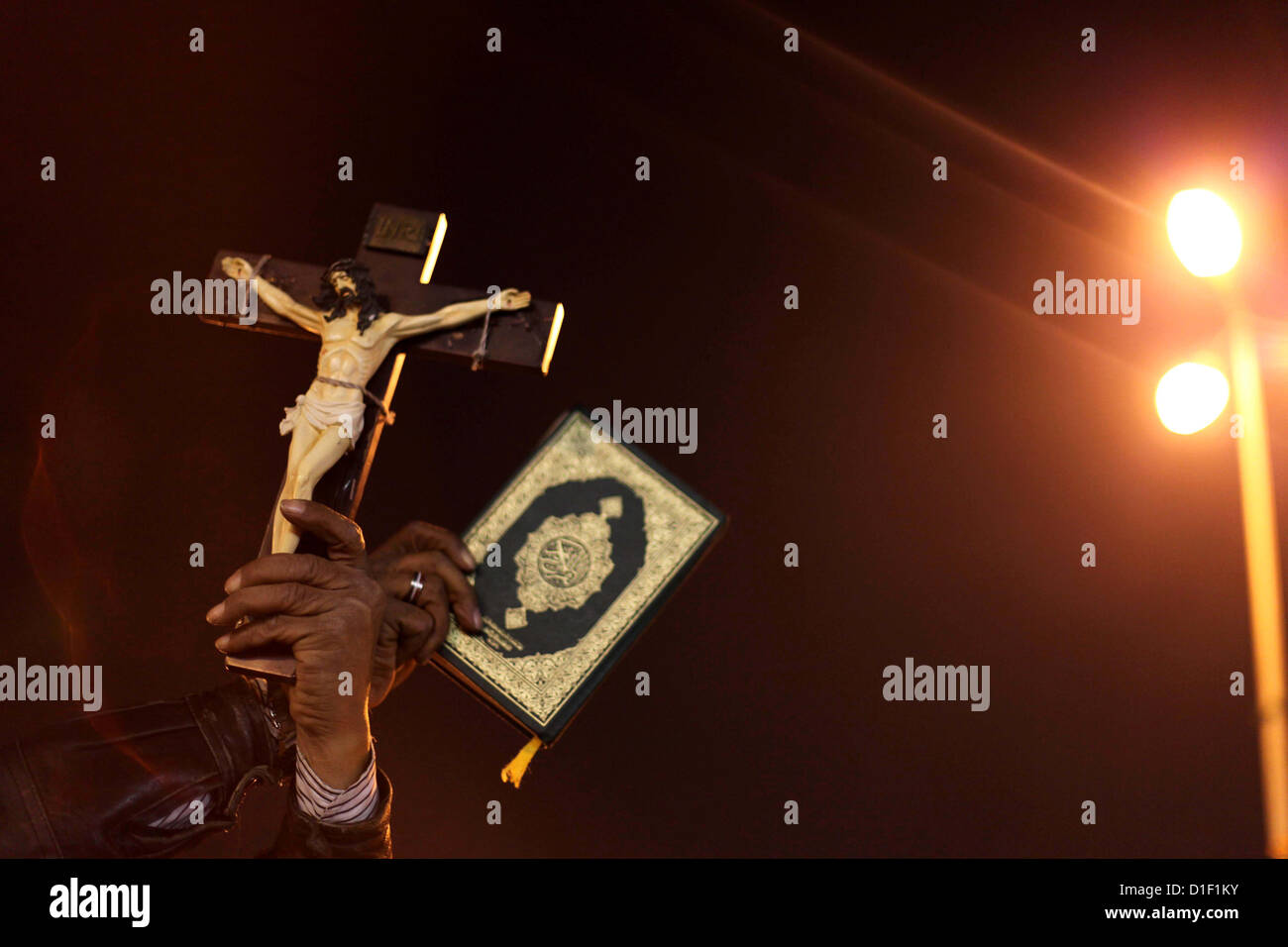 Dec. 18, 2012 - Cairo, Cairo, Egypt - A man holds a copy of the Koran and a cross as she shouts slogans during a Stock Photo