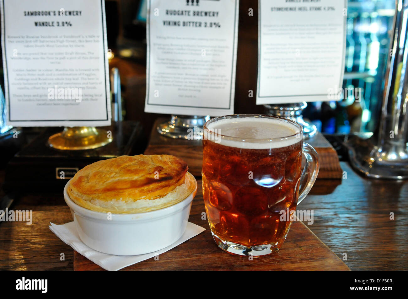 Pint of Ale and a Pie at The Draft House Pub, Northcote Road, Clapham, London, England, SW11 - Stock Image