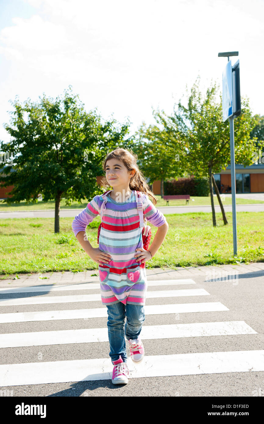 Girl crossing street at crosswalk on a closed course - Stock Image