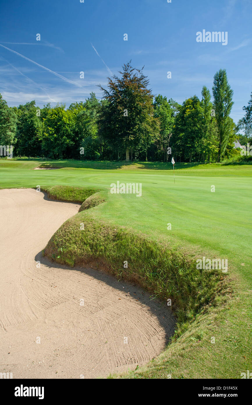 Bunker and golf green with flag, blue sky. - Stock Image