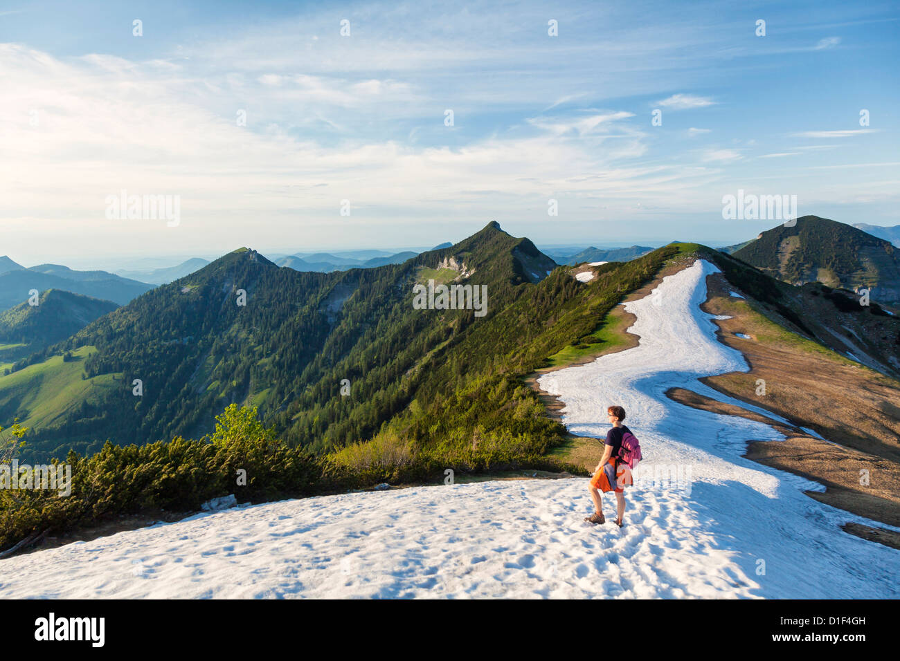Woman on snowfield in the Osterhorn Group, Salzkammergut Mountains, Austria - Stock Image