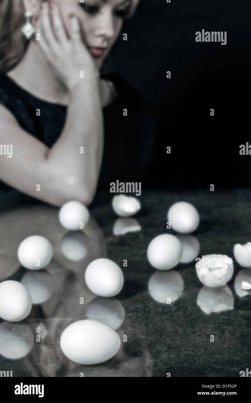 a woman is sitting at a table in front of several eggs, some of them broken - Stock Image