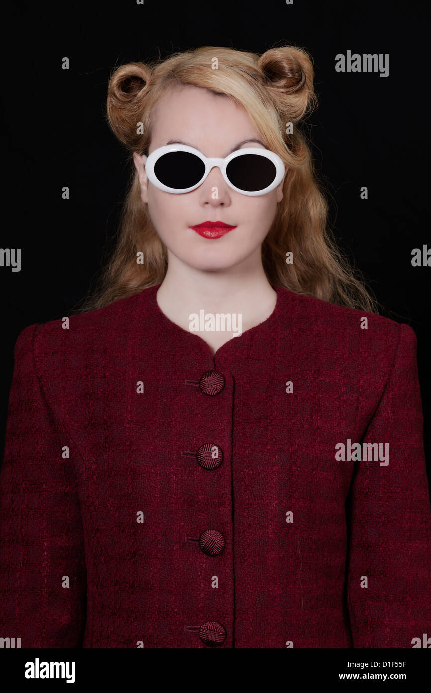 a woman in a vintage blazer with vintage sunglasses in 50s style - Stock Image