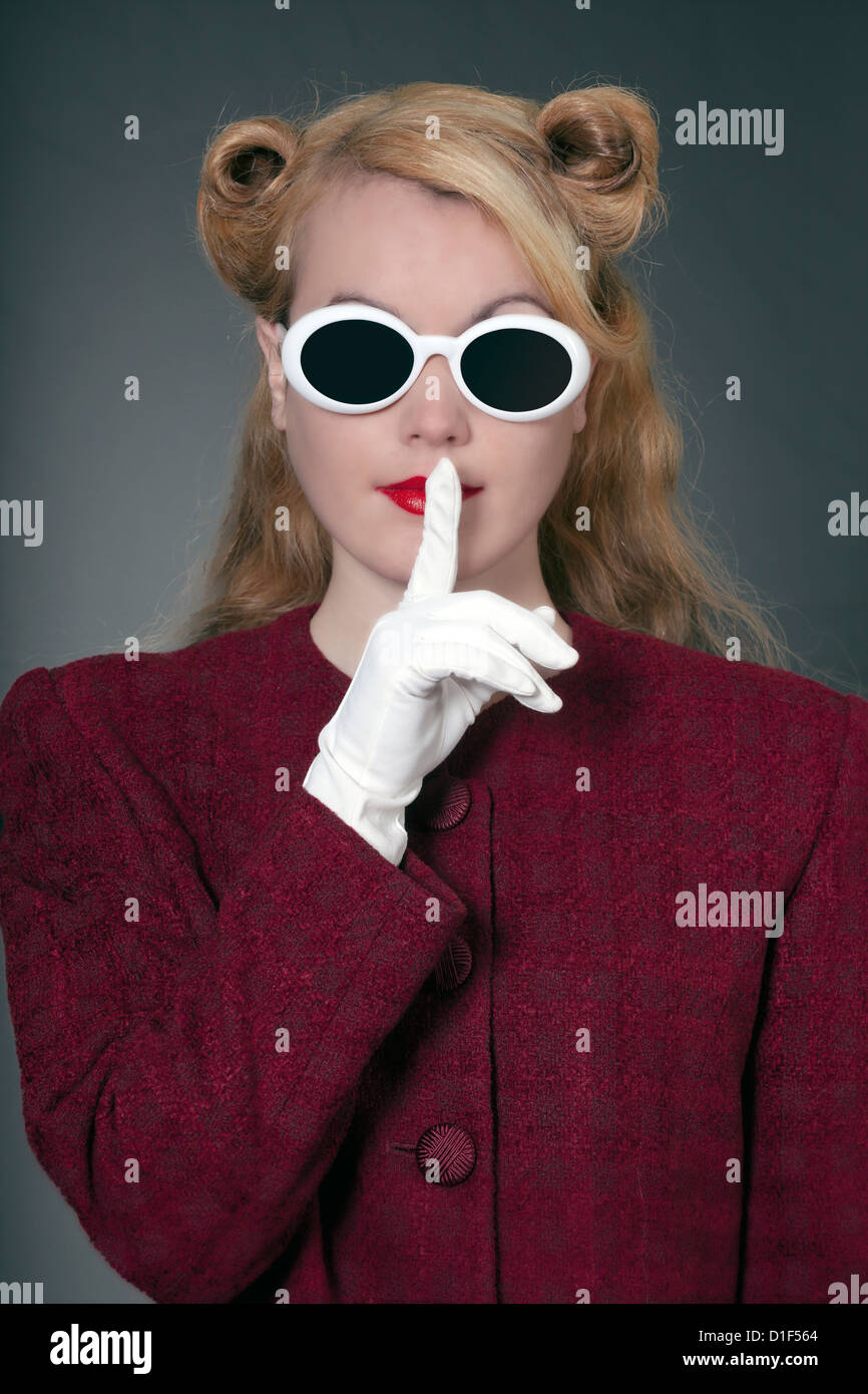 a woman in a vintage blazer with vintage sunglasses in 50s style with her finger on her lips - Stock Image