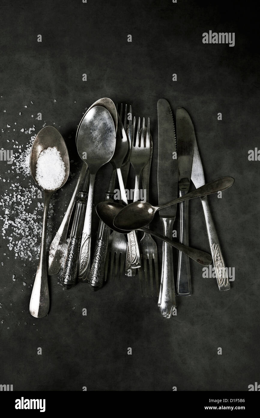 a collection of vintage silverware with coarse salt - Stock Image
