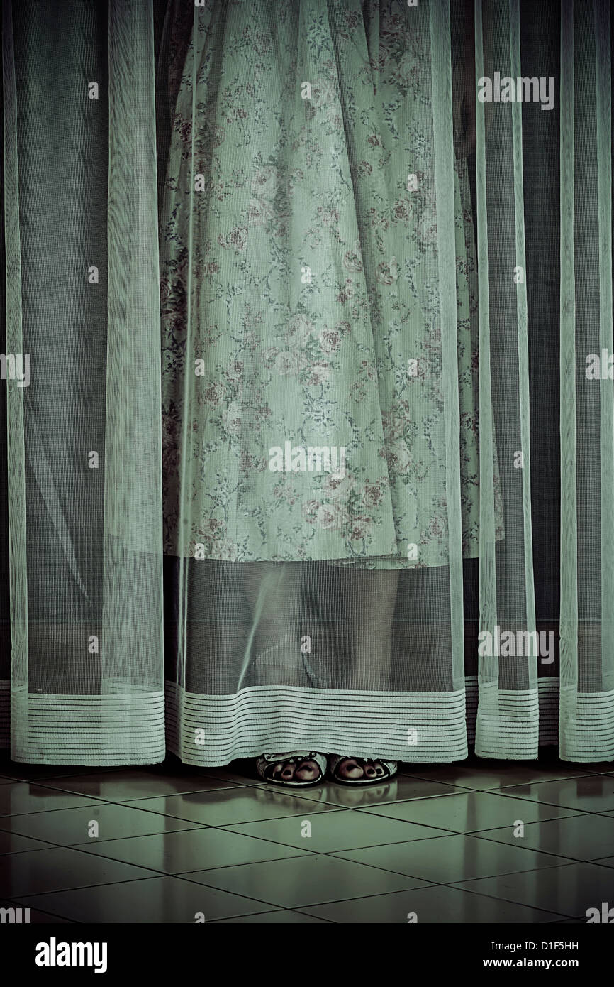 a girl is hiding behind a curtain - Stock Image