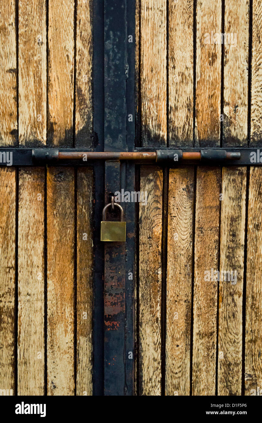 old wooden door closed and secured with a padlock - Stock Image