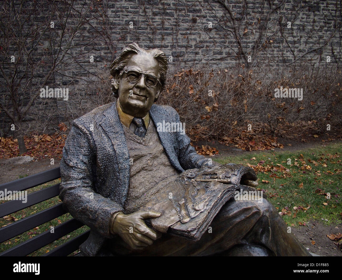 Statue of literary critic Northrop Frye on a park bench at Victoria College, University of Toronto - Stock Image
