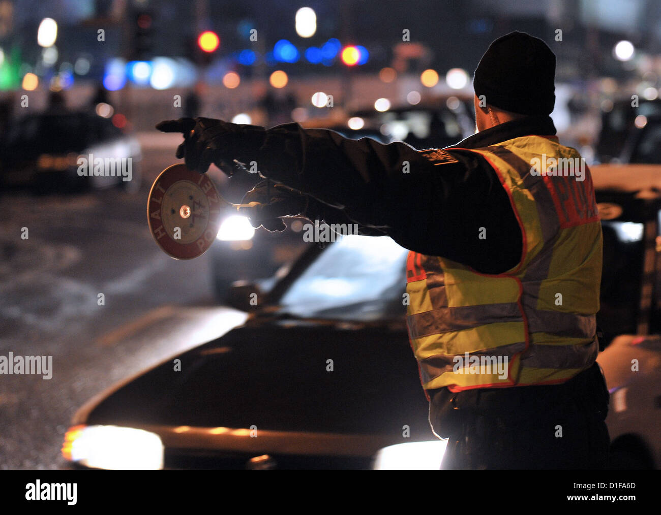 A police officer indicates to a driver to pull over in heavy traffic on the Alexanderplatz square in Berlin, Germany, - Stock Image