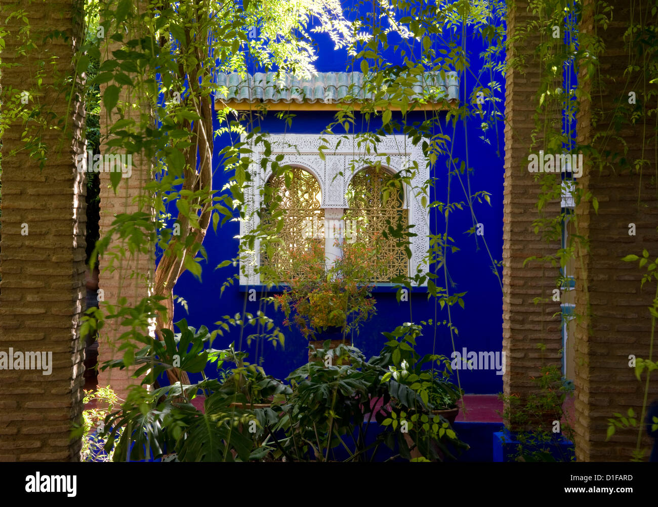 A view through a pergola to windows surrounded by blue walls at the Majorelle Garden in Marrakech, Morocco, North - Stock Image