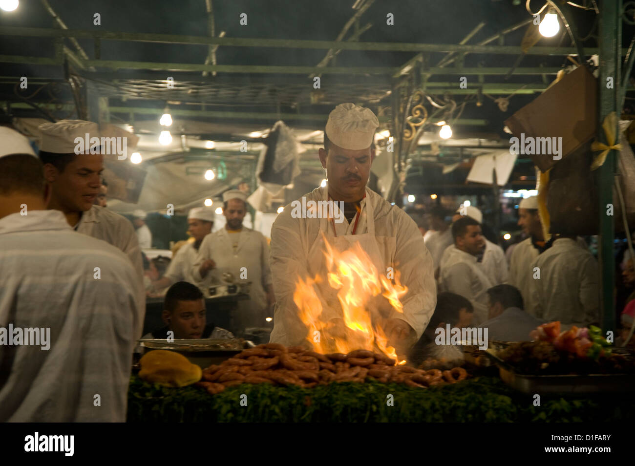 A chef grilling meat at food stalls in the main square, Jemaa el Fna, in Marrakech, Morocco, North Africa - Stock Image