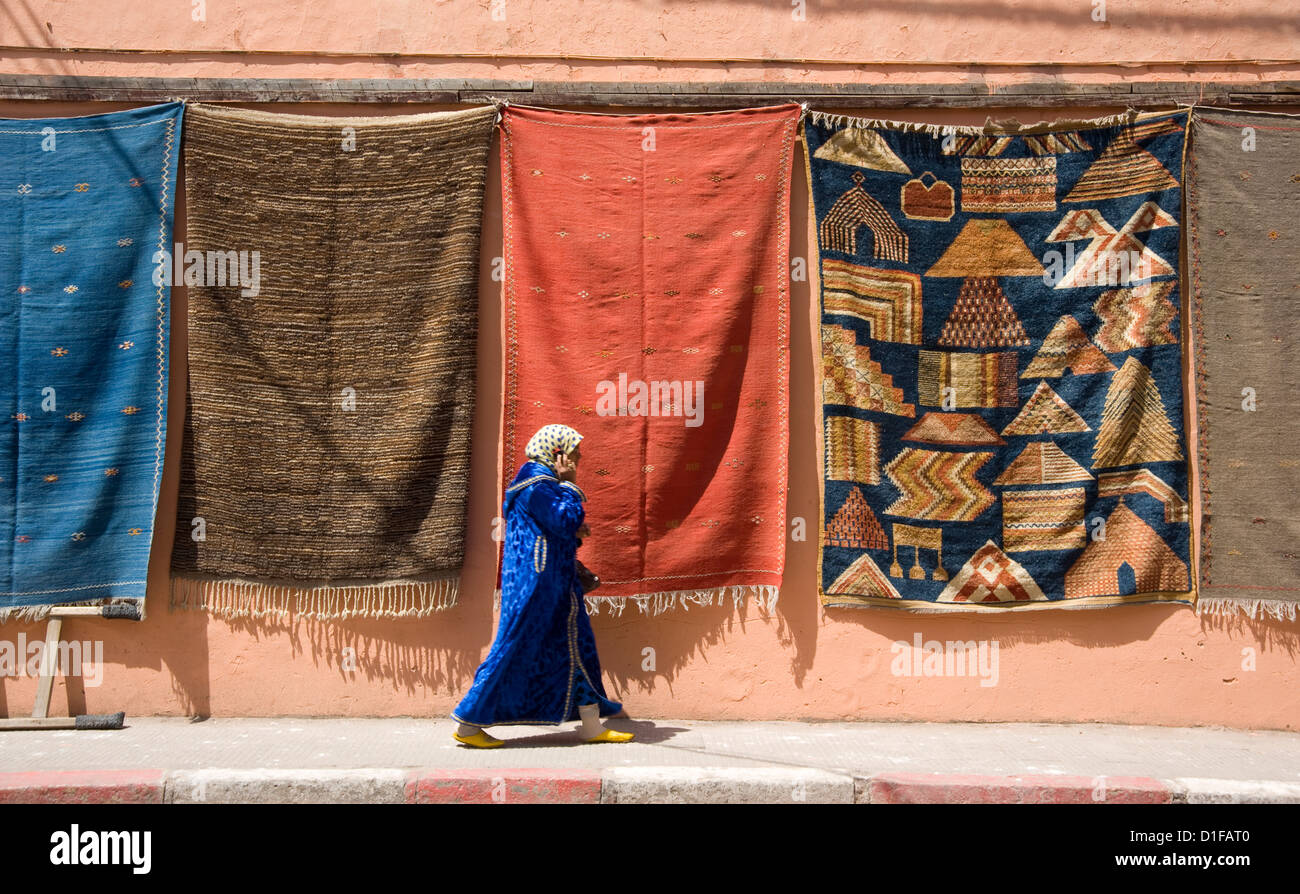 A woman in Islamic dress walking by a wall hung with carpets in the Medina in Marrakech, Morocco, North Africa, - Stock Image