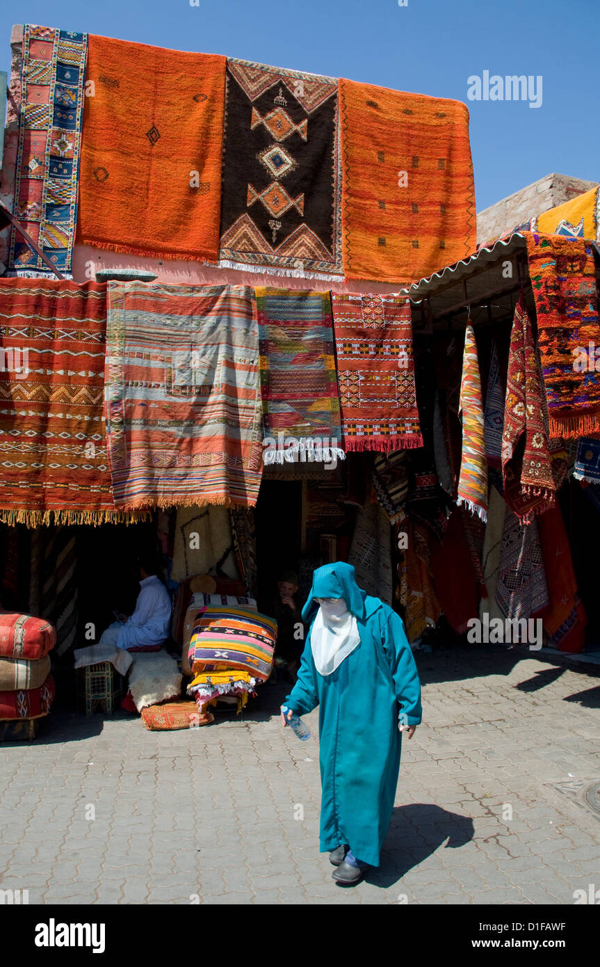 A woman in Islamic dress walking past carpets hanging around an entrance to the souk in Marrakech, Morocco, North - Stock Image