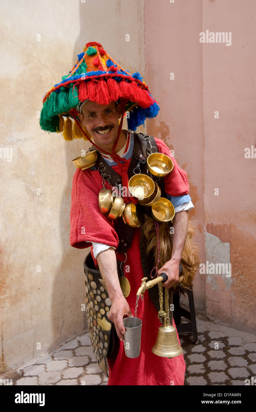 A water seller dressed in traditional colourful Berber dress in Marrakech, Morocco, North Africa, Africa - Stock Image