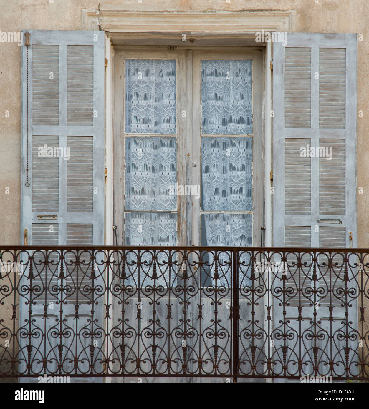 An old window, balcony and curtains in the picturesque village of Aregno in the inland Haute Balagne region, Corsica, - Stock Image