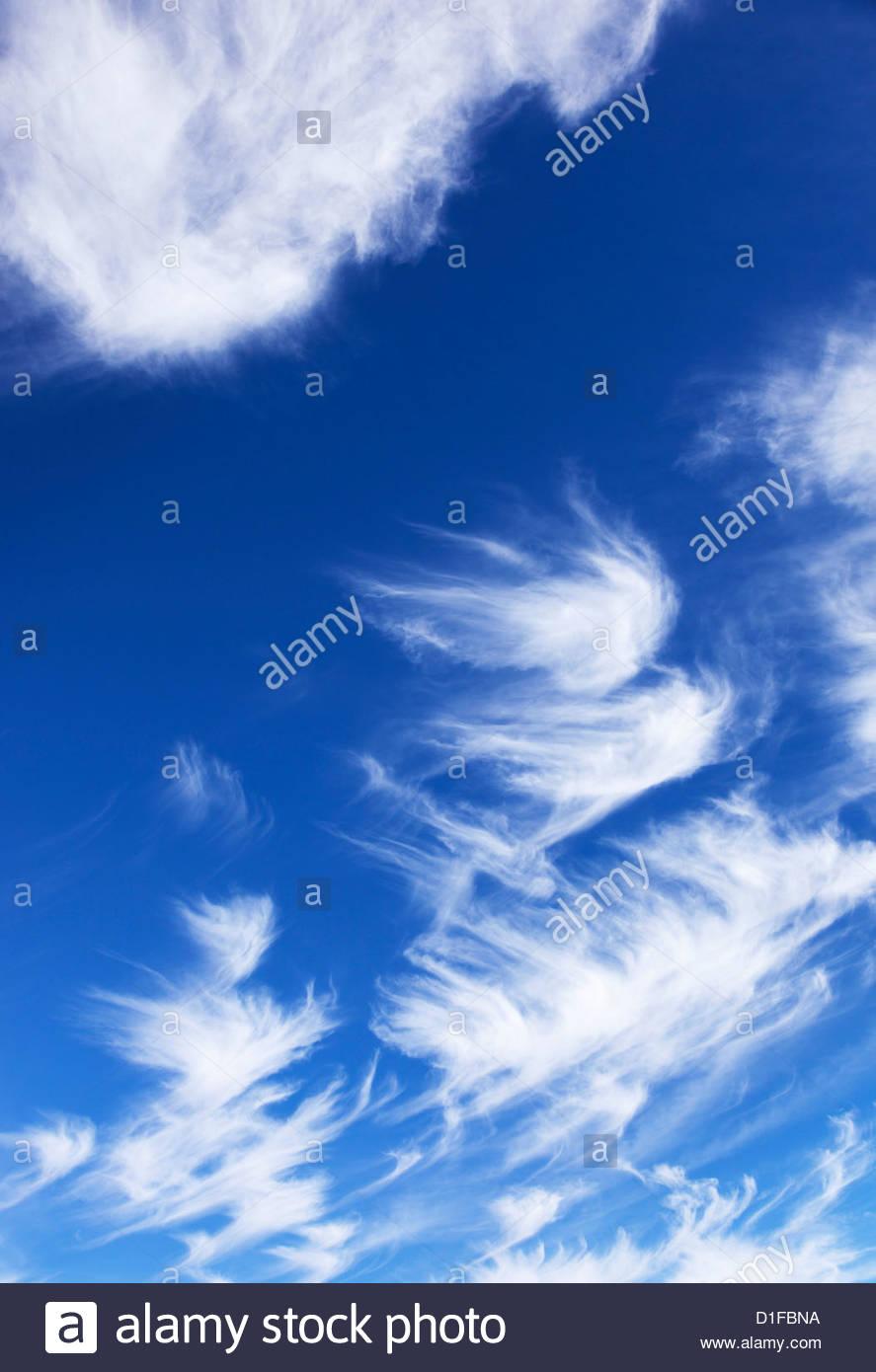 Thin wispy white clouds blue sky - Stock Image