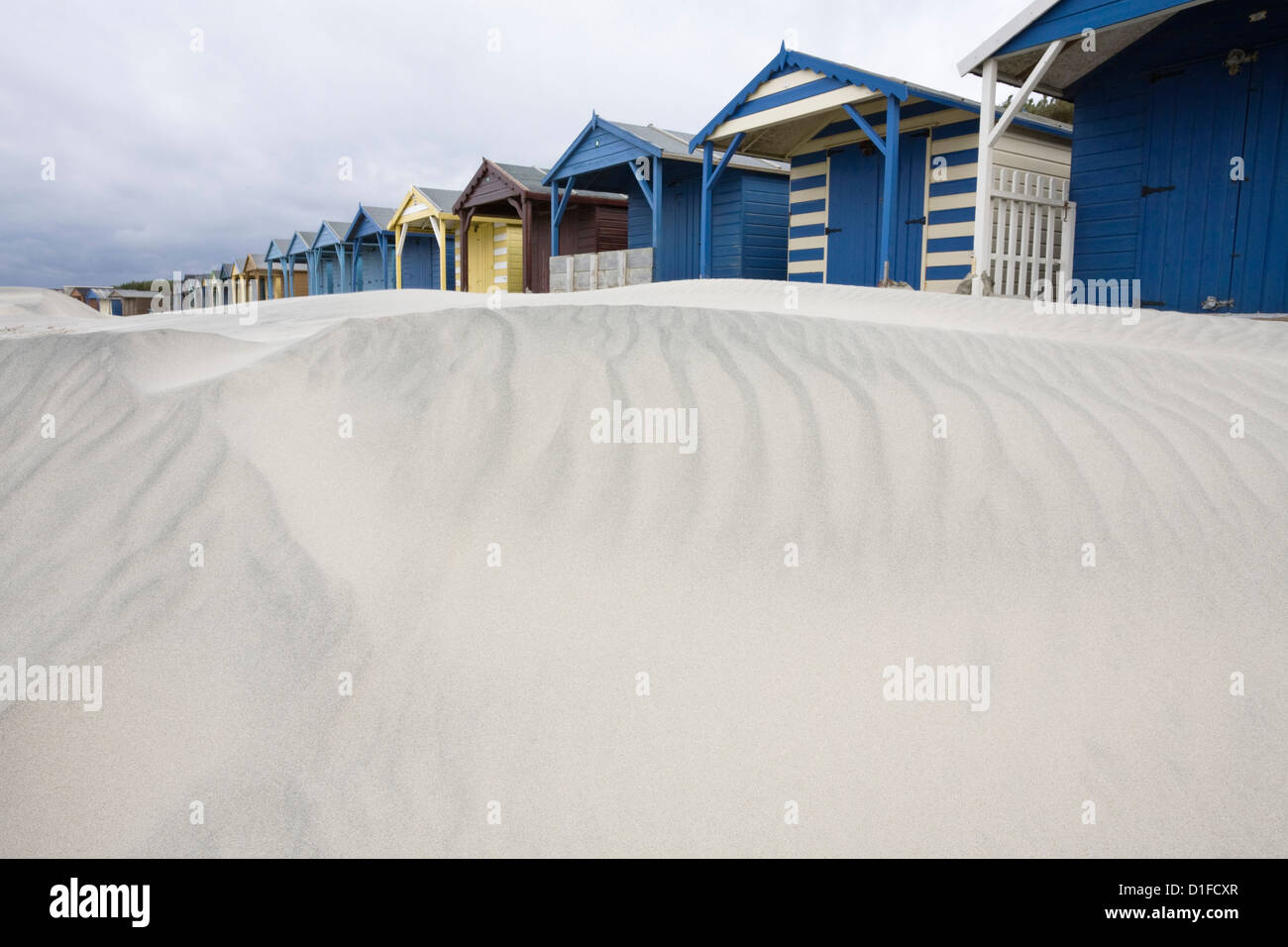 Beach huts in sand drift, West Wittering, West Sussex, England, United Kingdom, Europe - Stock Image