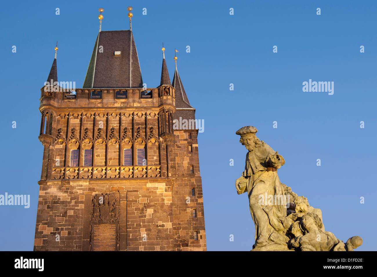 Town Bridge Tower and statue of St. Ivo (Bishop of Chartres) at twilight, Charles Bridge, Old Town, Prague, Czech - Stock Image