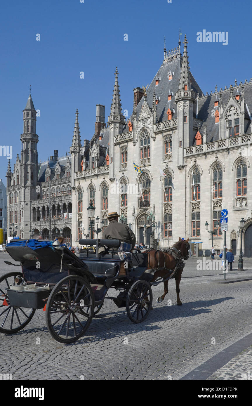 A horse drawn carraige drives past the Provincial Court Building in the Market Square, Brugge, Belgium, Europe - Stock Image