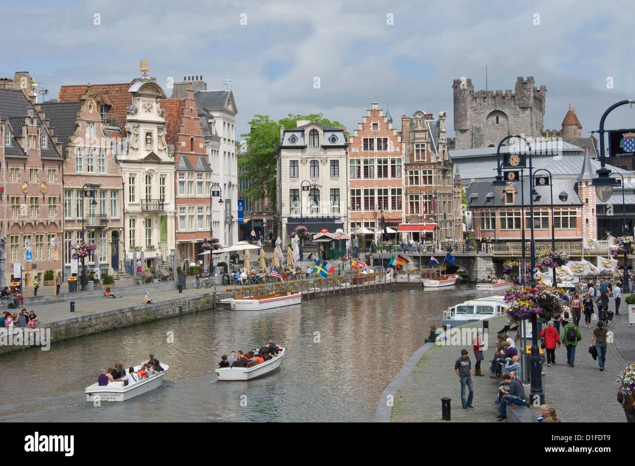Scene along the Graslei bank, lined with Flemish gabled houses, Gravensteen Castle beyond, in the centre of Ghent, - Stock Image