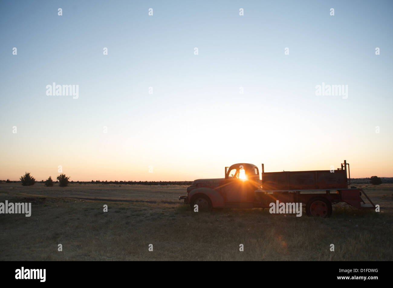 The sun beams through window of old farm truck at sunrise, Shaniko, California, United States of America, North - Stock Image