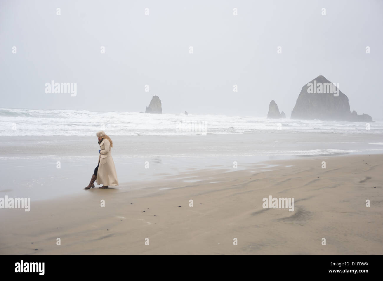 Woman talks on phone with Haystack Rock in the distance at popular tourist destination, Cannon Beach, Oregon, USA - Stock Image