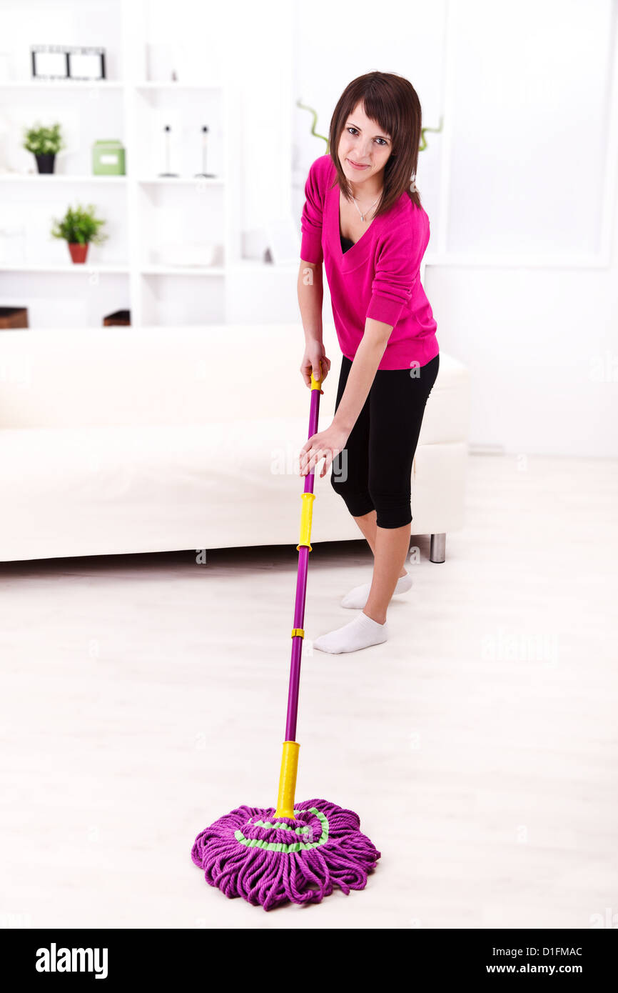 Attractive smiling woman cleaning the floor with a mop - Stock Image