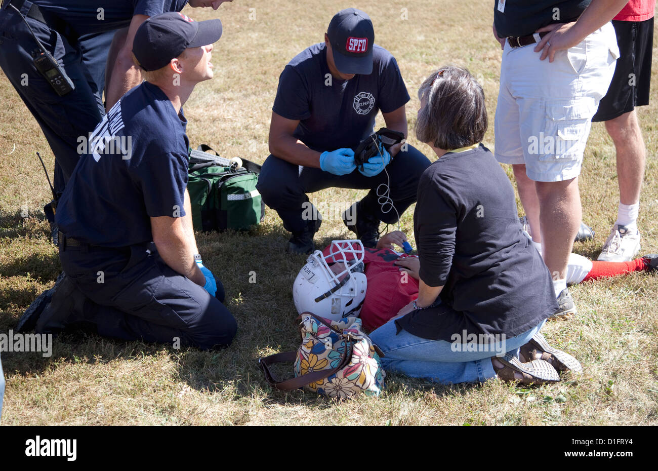 Nurse and paramedics attending to injured football player. Conway Height's Park St Paul Minnesota MN USA - Stock Image