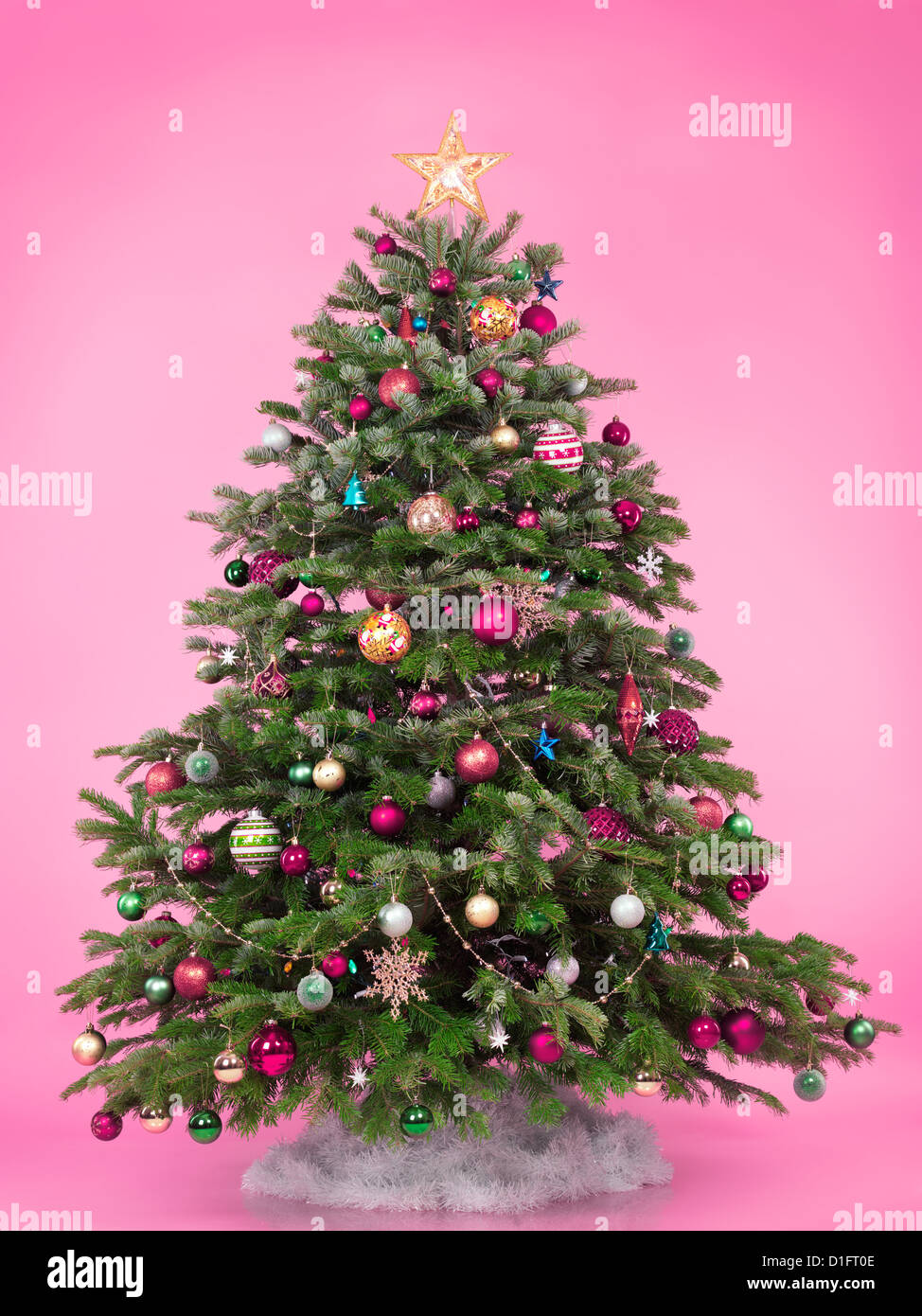 Decorated Christmas tree isolated on cute pink background - Stock Image