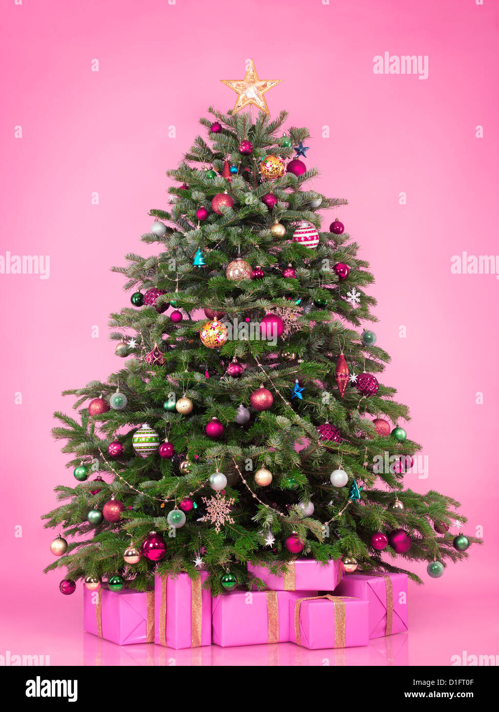 Decorated Christmas tree with presents and gift boxes isolated on pink background - Stock Image