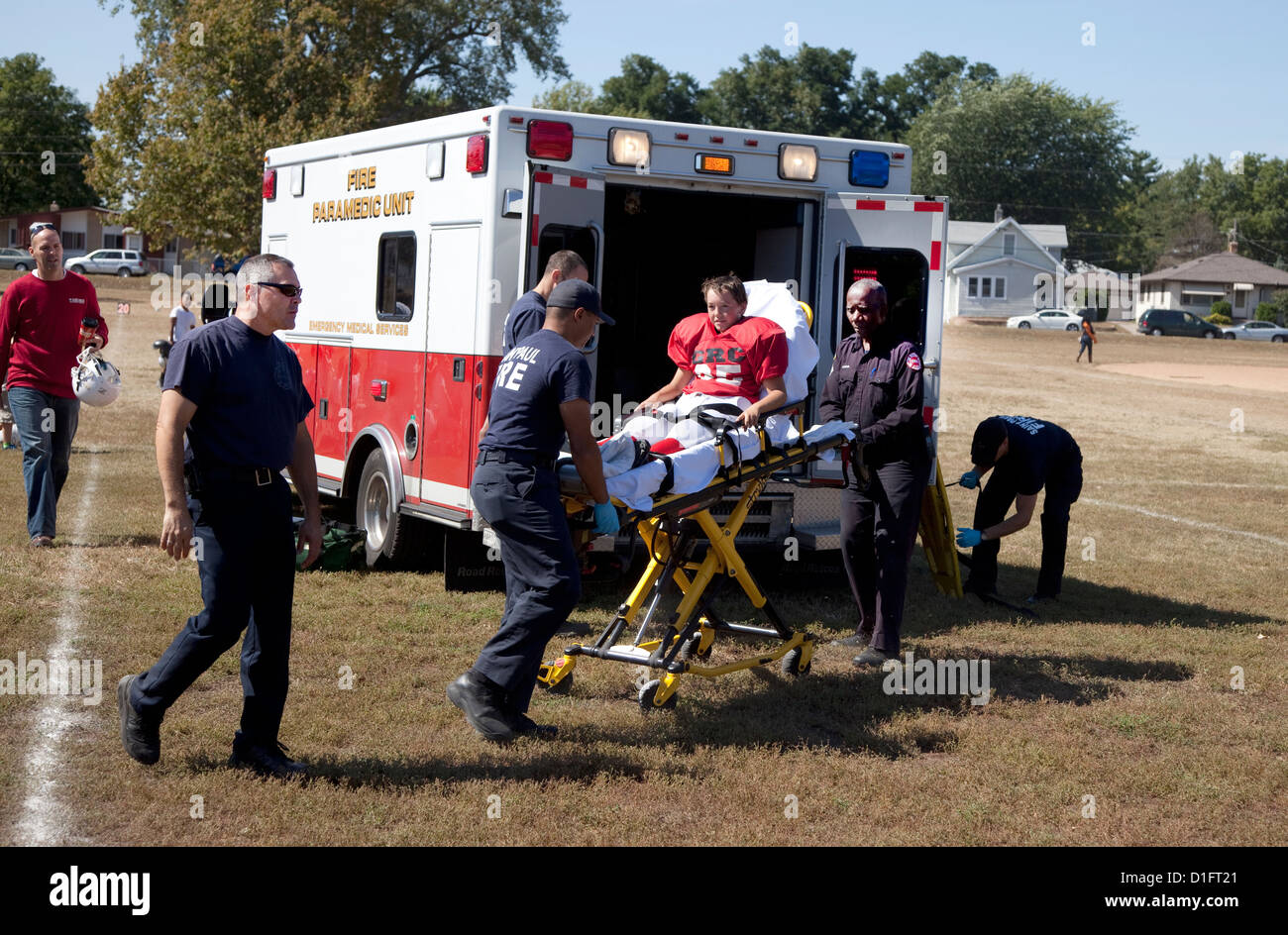 Paramedics wheel football player with possible concussion to emergency vehicle. Conway Height's Park St Paul - Stock Image