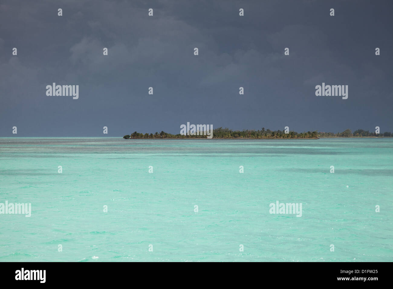 Black skies from a huge storm over the clear turquoise waters of the Caribbean near Belize. - Stock Image