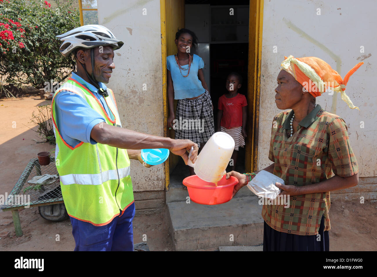 A volunteer of the Leoni´s Care Center NGO in Tsumeb/Namibia brings soup to the poor of a township - Stock Image